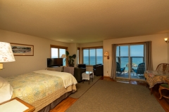 Room One with bed, chairs, couch and wonderful ocean views.