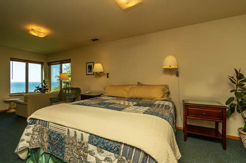 guest room with bed, chairs, couch and view - redwood national park lodging on the northern california coast with oceanviews